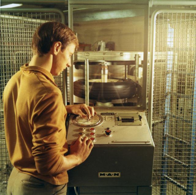 Renkaan rakenteellista kestävyyttä testataan koestuskoneella 1970-luvulla.