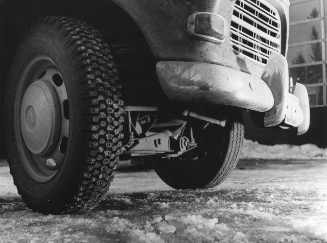 Испытание грузовика с зимними и лентими шинами. Ответственный водитель устанавливает зимние шины на все колеса.
